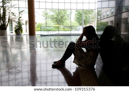 A young girl sitting on floor feeling devastated after hearing of bad news in her life. - stock photo