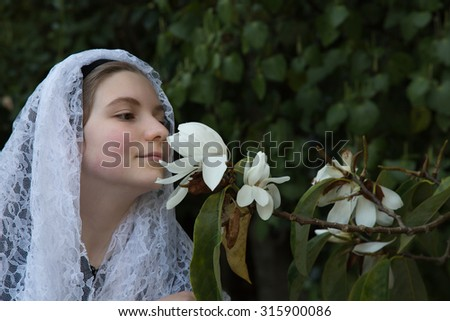 A young girl smells a freshly opened, white magnolia blossom. The first signs of spring and her youthful innocence is a stunning scene. This photo could be used for a variety of ideas and concepts. - stock photo