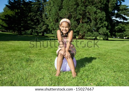A young girl smiles big while in a park, sitting on a ball. - horizontally framed - stock photo