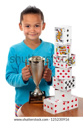 A young girl smiles with a trophy in her hands. She won a card building competition. - stock photo