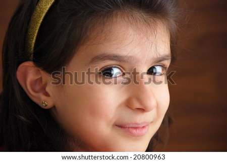 A young girl smiling and looking at you