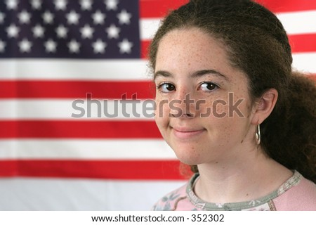 A young girl smiling in front of an American flag.