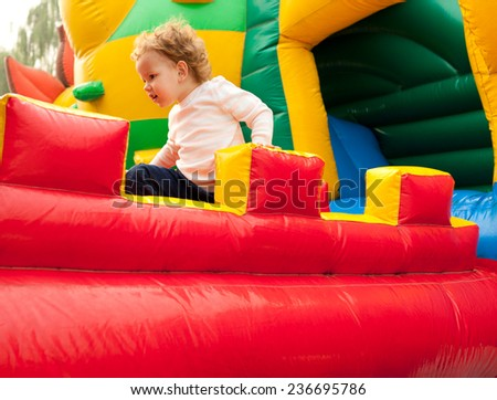A young girl smiling on inflatable playground - stock photo