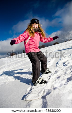 A young girl snowboarding in the Alps, outdoor shoot. - stock photo