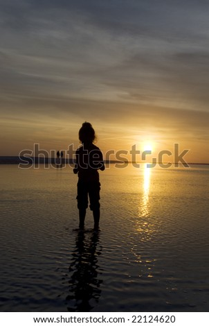 A young girl staring curiously at the ripples in a wading pool as the sun sets beautifully in the background