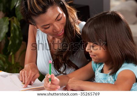 a young girl studies while her mom helps - stock photo