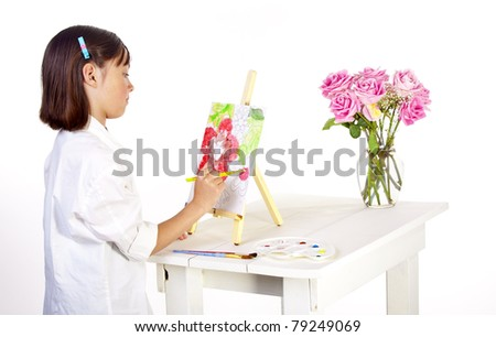 A young girl tries to paint a picture of a vase of flowers on a pre-sketched canvas. - stock photo