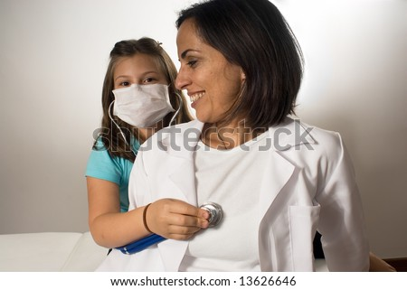 A young girl wearing a doctor's mask listens to the doctor's heartbeat with a stethoscope while the doctor sits on an examining table. Horizontally framed photograph - stock photo