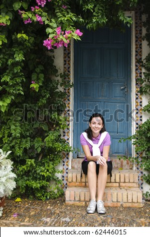 A young girl wearing sporty clothes sitting on steps with a blue door behind her. - stock photo