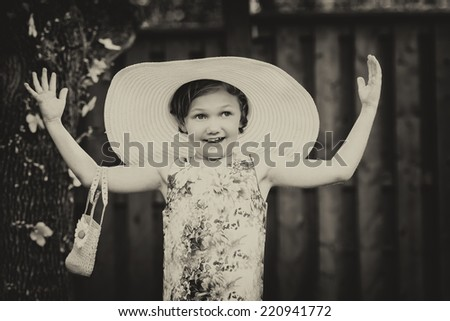 A young girl with a happy expression holds her arms out wearing a white over-sized sun hat outside on a sunny spring day.  Filtered and toned for a retro, vintage look.  - stock photo