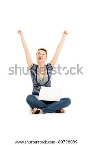 A young girl with a laptop sitting on the floor, hands up - stock photo