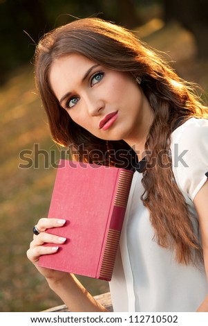 A young girl with book in the park - stock photo