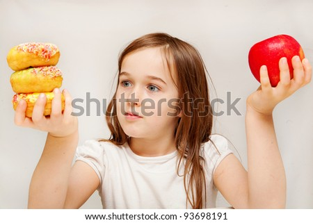 A young girl with food contemplates whether she would prefer healthy apples or unhealthy donuts. - stock photo