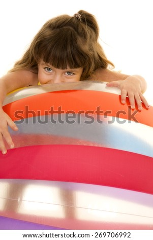 a young girl with her face laying on a big beach ball. - stock photo