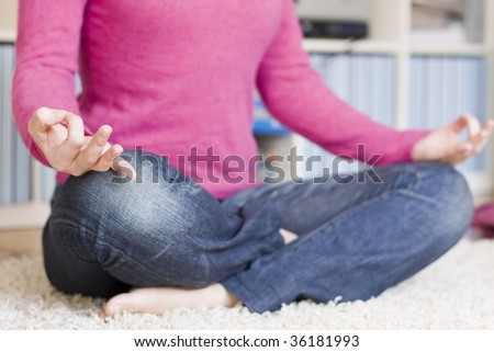A young girl with pink pullover is meditating on her carpet at home. Candid shot. Focus on the models right hand, very shallow DOF. - stock photo