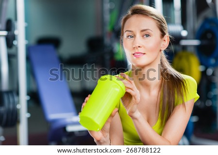 A young girl with water in gym  - stock photo