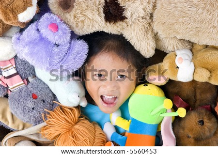 A young girls in the middle of alot of stuffed animals.