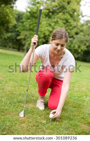 a young golfer placing the ball on the tee - stock photo