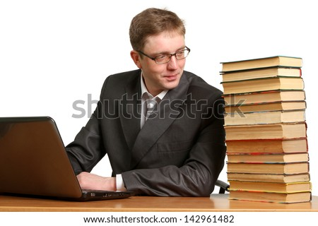 A young guy can not determine the choice where to get information from a laptop or paper books isolated on white background