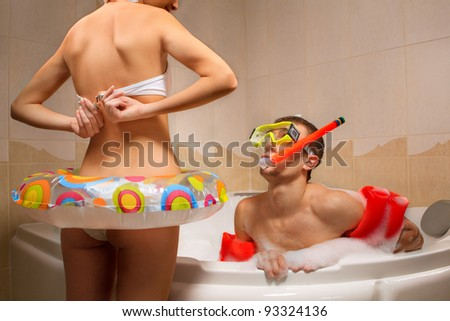 A young guy sitting in front undressing girl in bath in mask with snorkel. He is looking confused and shocked. - stock photo