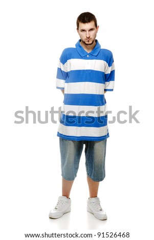 A young guy with a beard, wearing shorts, sneakers and football shirt, isolated on a white background. - stock photo