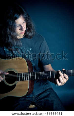 A young guy with long hair playing on an acoustic guitar against a dark background - stock photo