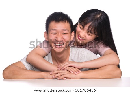 A young handsome asian man being hugged from behind by his beautiful girlfriend siting behind the table with smling