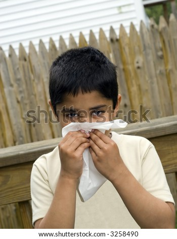 A young handsome boy with a tissue to his nose nurses a cold - stock photo