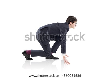 A young handsome businessman wearing a suit and glasses at crouch start ready to run. Concept of readiness - stock photo