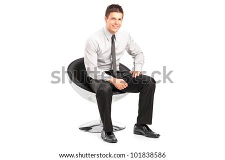 A young handsome malesitting on  chairand posing isolated on white background - stock photo