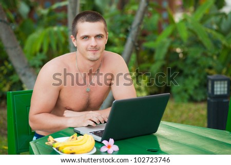 A young handsome man sitting at the green table with laptop - stock photo