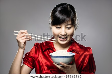 A young happy Asian girl eating rice with bowl and chopsticks