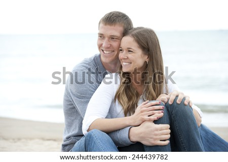 A young happy caucasian couple sitting on the sand at the beach on a sunny day. - stock photo
