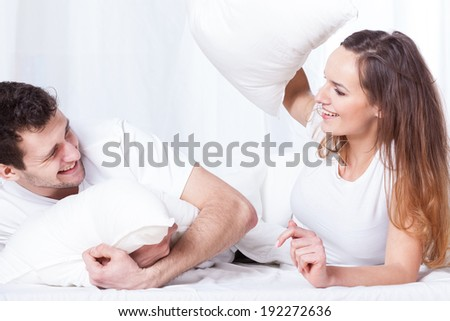 A young happy couple having a pillow fight in bed