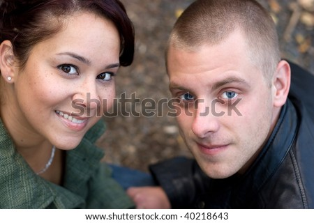 A young happy couple outdoors on a fall day. - stock photo