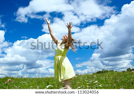 A young happy girl with streaming in the wind hair, in a yellow dress, is throwing in the air camomile petals and smiling. Freedom concept. - stock photo