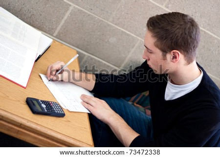 A young high school or college student working on his math homework. - stock photo