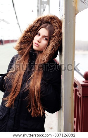 A young hipster woman in the city. View over bridge, outdoors, winter time - stock photo