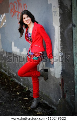 A young hispanic teen woman leans against a wall, smiling, in an urban setting. - stock photo