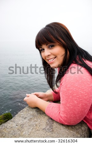 A young hispanic woman with red highlights in her hair by the sea shore in Newport Rhode Island. - stock photo