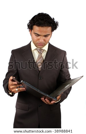 A young Indian businessman checking documents in a file, on white studio background. - stock photo