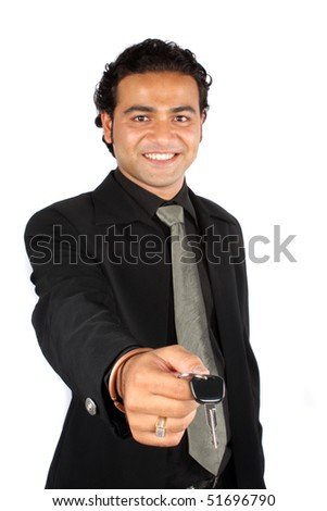 A young Indian businessman handing over the keys of a new car to a customer, isolated on white studio background. - stock photo