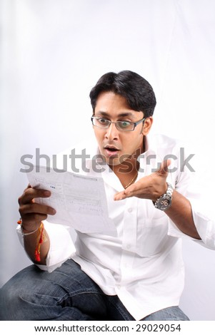 A young Indian businessman shocked looking at the billed amount. - stock photo