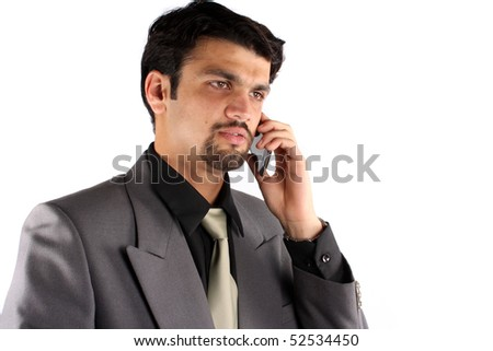 A young Indian businessman talking on his cellphone, on white studio background.