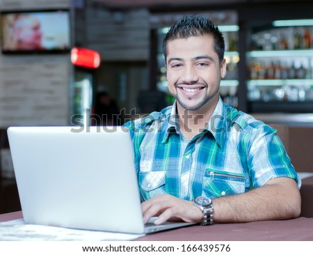 A young Indian guy in a cafe working on laptop - stock photo
