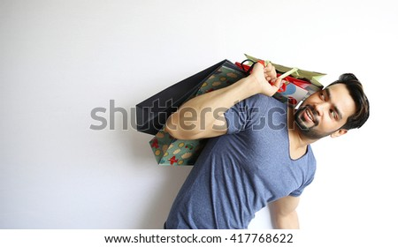 A young Indian man holding shopping bags on white background. - stock photo