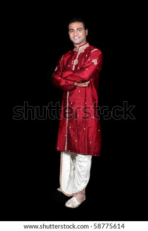 A young Indian man in a traditional attire, on black studio background. - stock photo