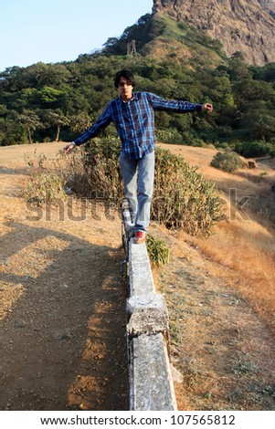 A young Indian man trying to balance himself while walking on a cement beam. - stock photo