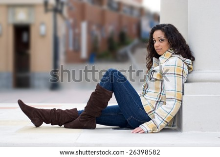 A young Indian woman posing outdoors in an urban setting. Shallow depth of field. - stock photo