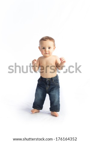 A young infant boy learns to walk on a white background - stock photo